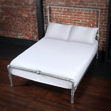Bed featuring fluidproof white fitted sheet and matching pillowcases.which are now available.