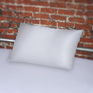 White fluidproof pillowcase on bed with silver frame against brick wall