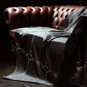 Black Throw printed with black leather straps draped over a red Chesterfield sofa