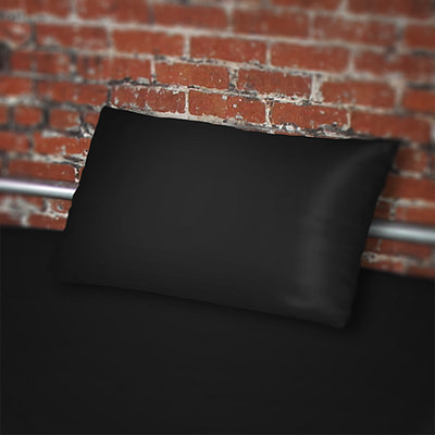 Fluidproof Black pillowcase on bed against a brick wall